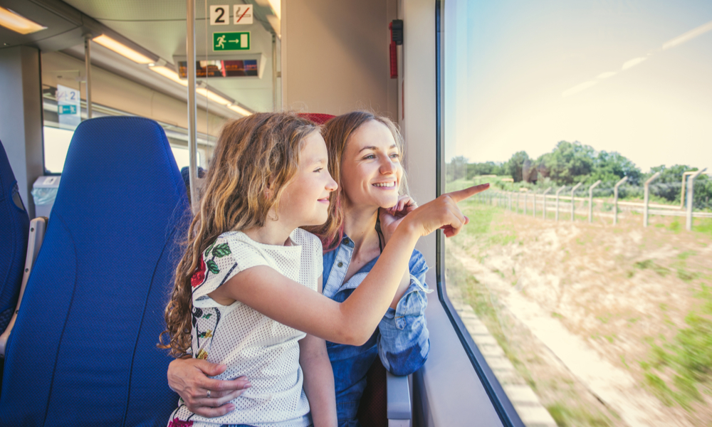 How to Save When You're Traveling with Kids: Family traveling in a train and looking through the window
