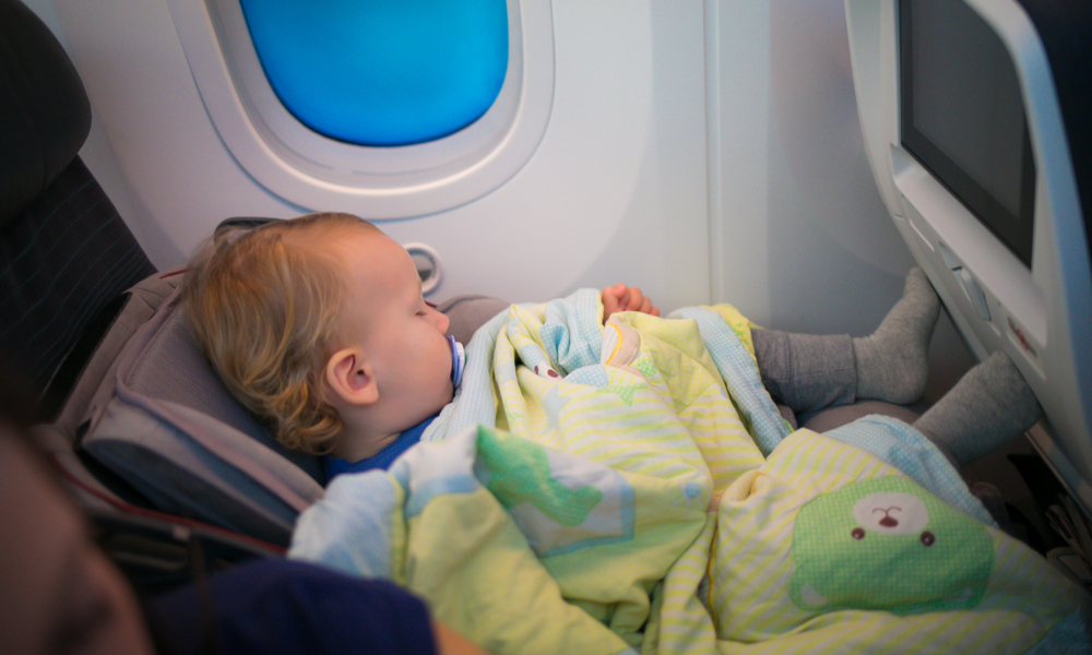 baby sleeping in her own car seat setting on an ordinary seat on a commercial airliner.