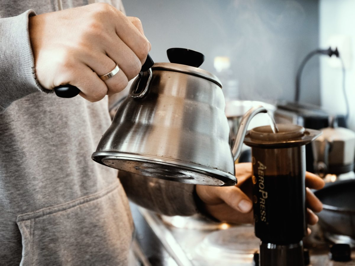 Photo of a man making Aeropress coffee by Alex Chernenko from Unsplash