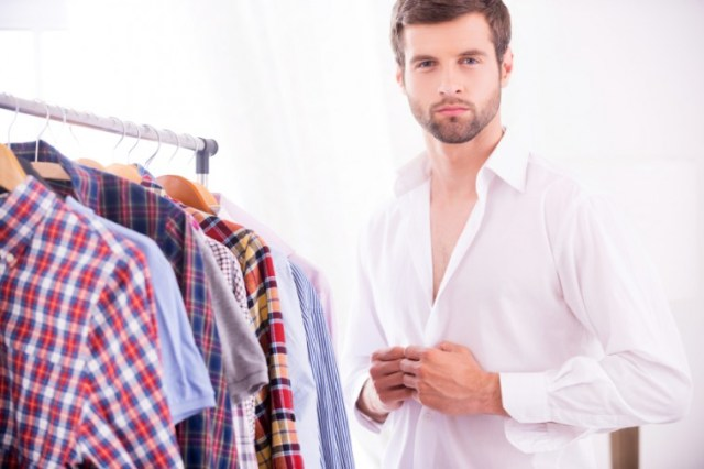 man getting dressed next to his shirts