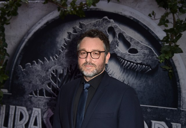 Colin Trevorrow, standing in front of a Jurassic World poster on the red carpet