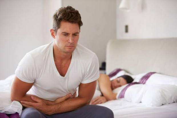 Man holding stomach as he struggles with constipation