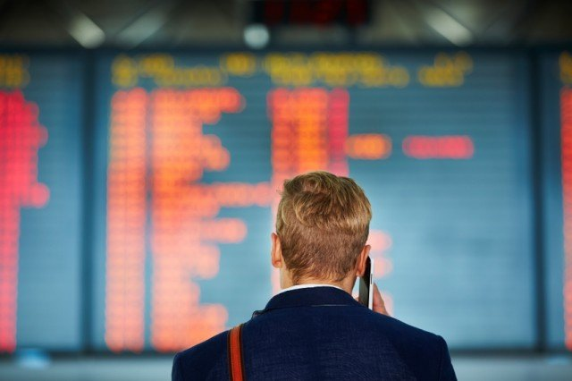 man on phone looking at flight board