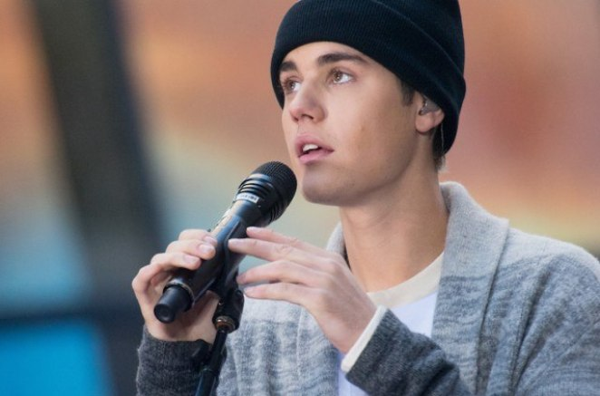 Young man in a black cap and gray sweater holding a microphone