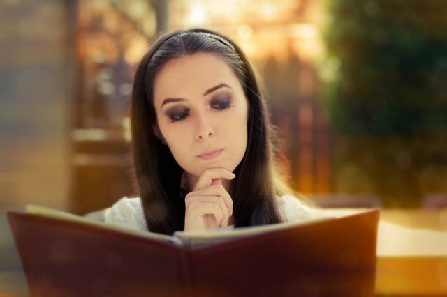 Woman reading Chinese restaurant menu to decide which Chinese food to order