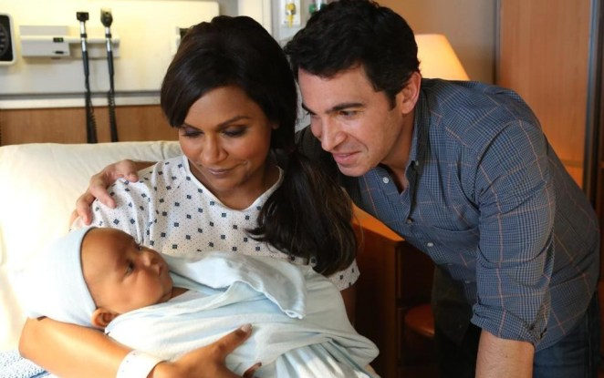 Mindy Kaling holds a baby while Chris Messina looks on in a scene from The Mindy Project