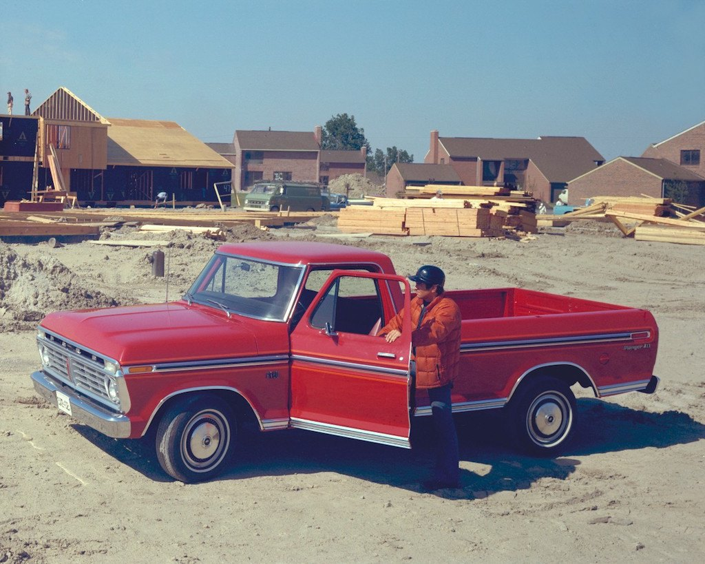 a red 1975 ford f 150 sits parked in front of a construction site [ 1024 x 819 Pixel ]