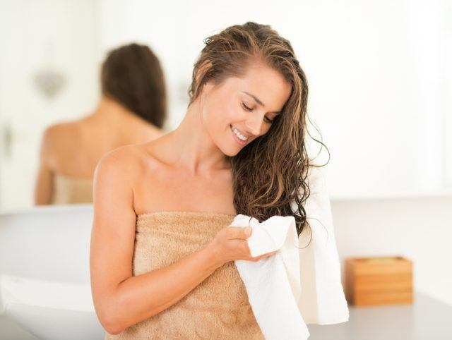 young woman wiping hair with a towel