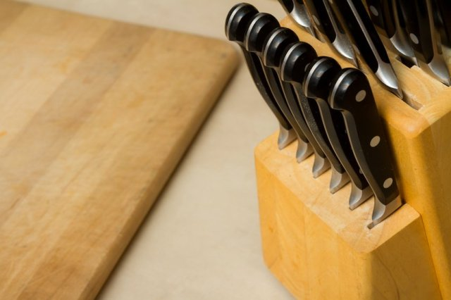 bunch of knives with a cutting board