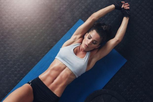 Muscular woman doing stretching workout on exercise mat