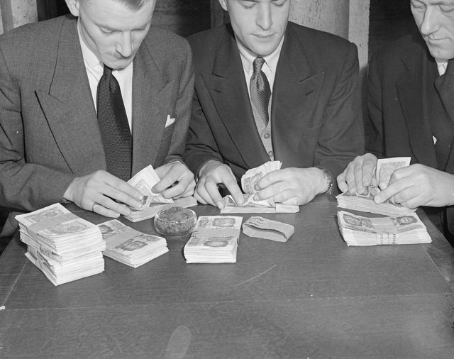 Men counting cash and discussing the concept of financial security
