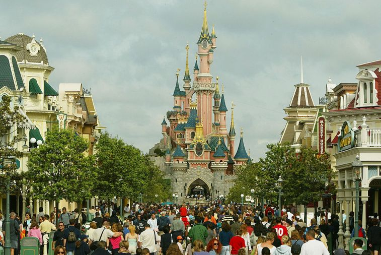 tourists walk toward the Sleeping Beauty castle on the main street at Disneyland Paris