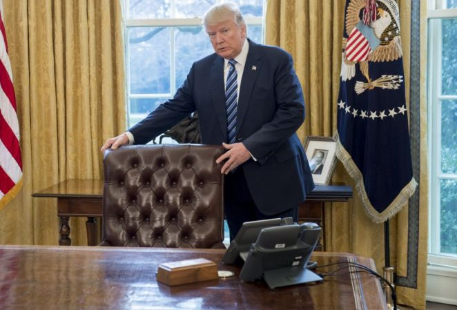 Donald Trump stands behind his desk