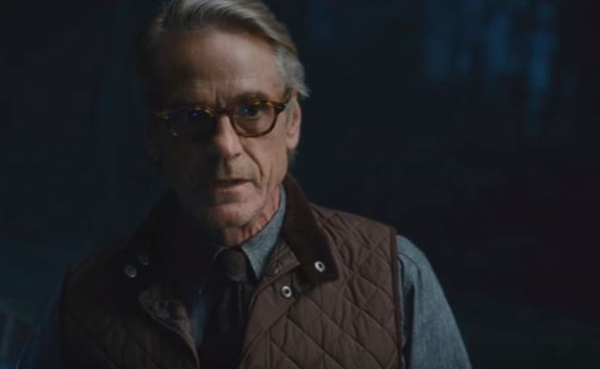 Alfred looks ahead while wearing a vest and glasses