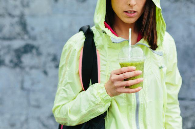 A woman stands in a green running jacket holding a green smoothie.