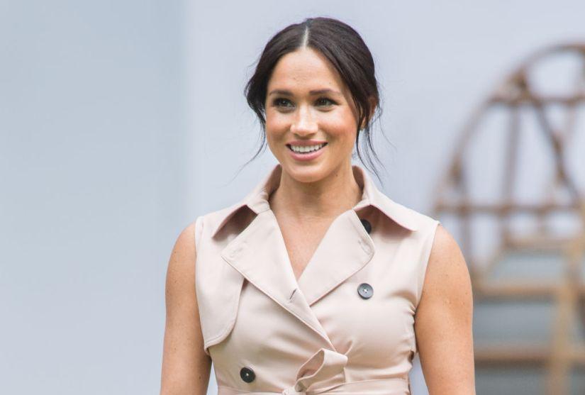 Meghan Markle smiles in a beige dress