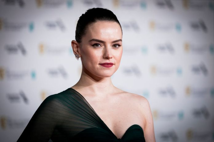 Daisy Ridley smiling in front of a repetitive background