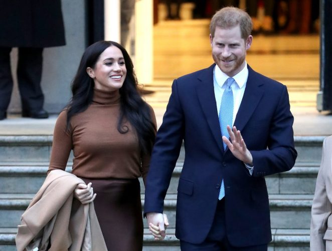 Meghan Markle smiling, looking to the side, holding hands with Prince Harry