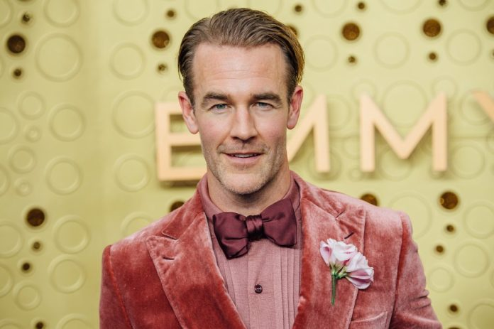 James Van der Beek smiles in front of a yellow background