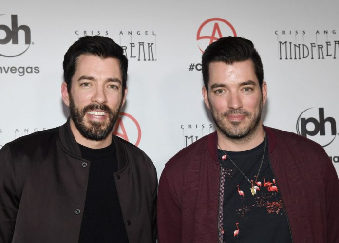 (LR) Drew Scott and Jonathan Scott smiling in front of a white background