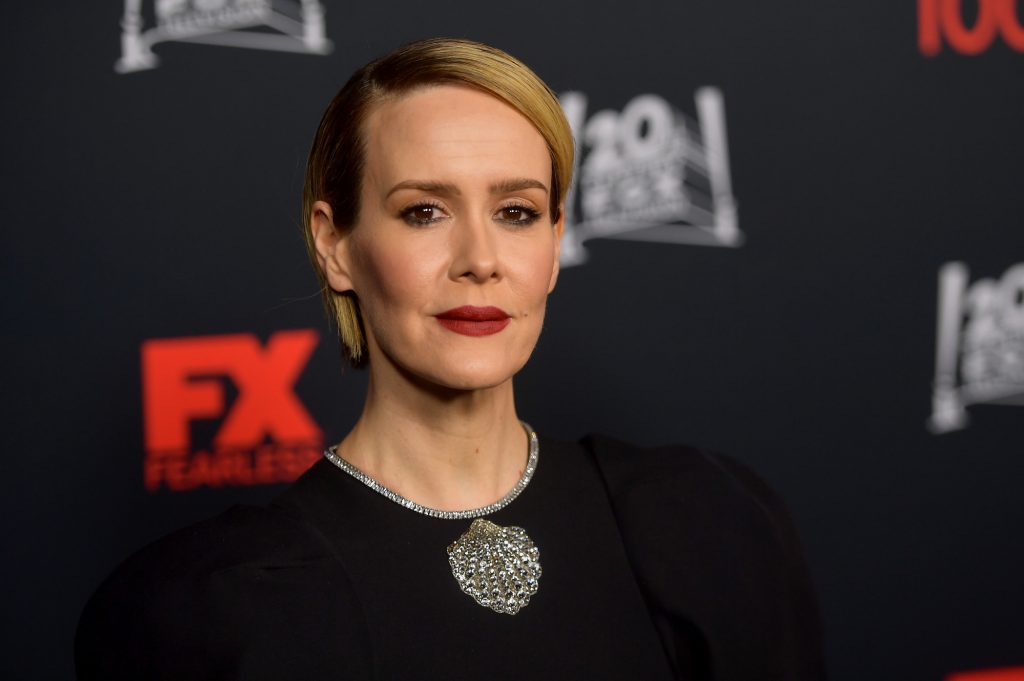 Sarah Paulson smiled a little in front of a black background