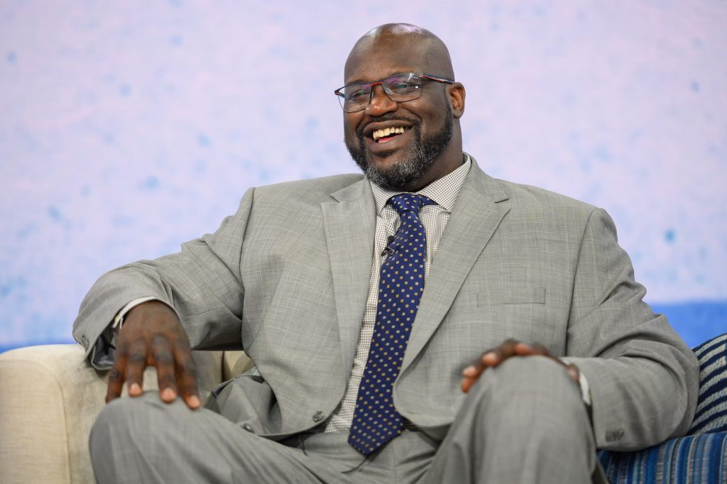 Shaquille O'Neal smiling, sitting down, in front of a white background
