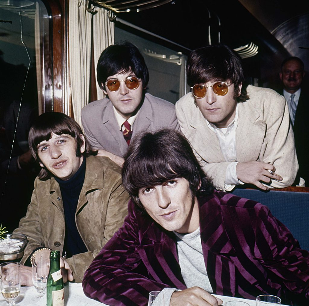 The Beatles have suits near a bottle