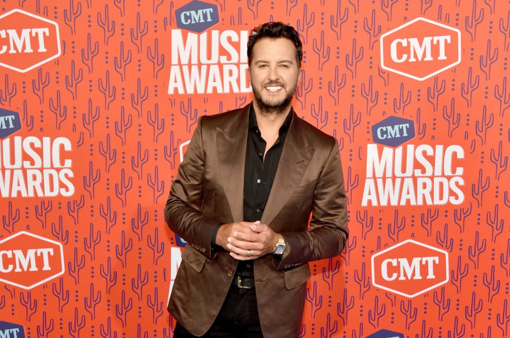 Luke Bryan smiling in front of an orange background
