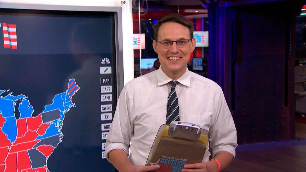 Steve Kornacki smiles at the camera in front of a selection map
