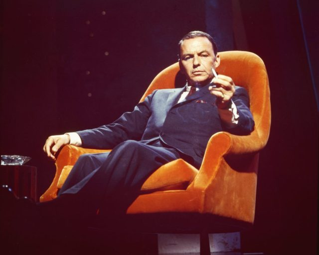 Frank Sinatra poses for a photo in an armchair