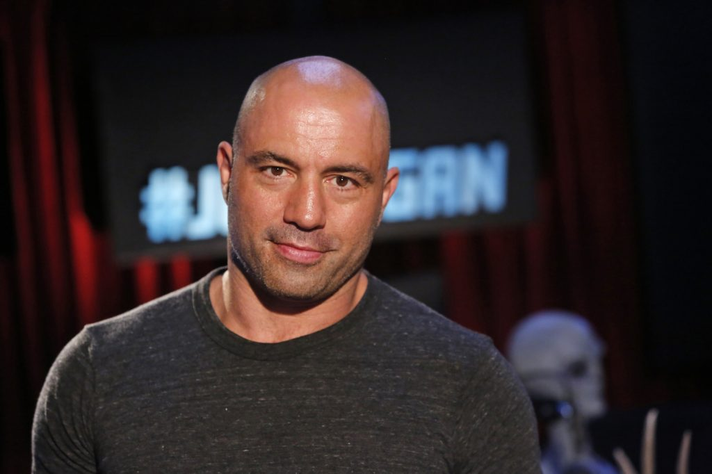 Joe Rogan smiles in front of a dim background