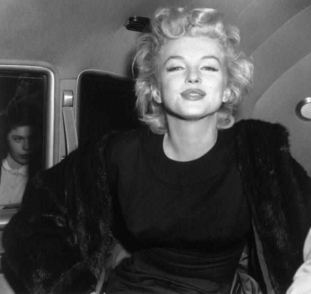 Marilyn Monroe smiles for a photo in the back of a car