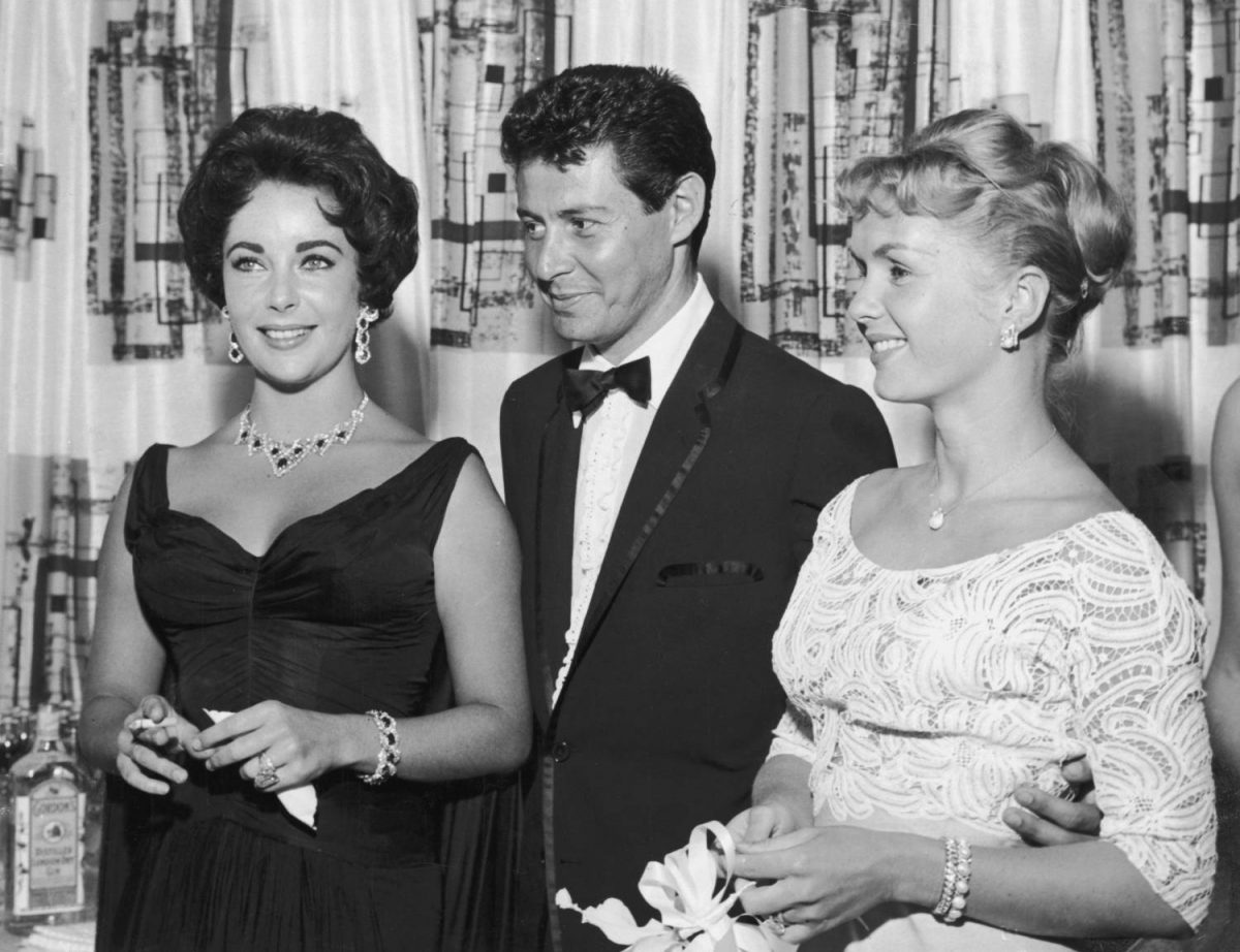 American singer Eddie Fisher, wearing a tuxedo, stands with arms around his wife, American actress Debbie Reynolds (R) and smiles as he watches British-born actor Elizabeth Taylor, cigarette smoking, Las Vegas, Nevada.  The following year Fisher left Reynolds and married Taylor.