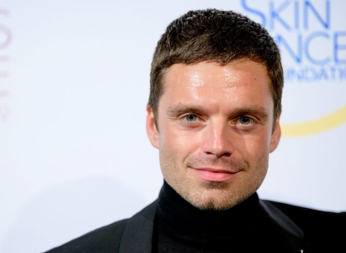 Smiling Sebastian Stan in front of a white background