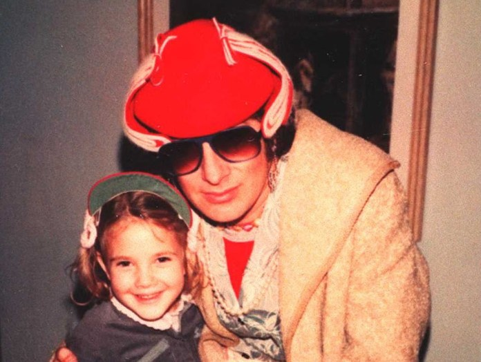 Drew Barrymore as a child with Steven Spielberg in sunglasses and a hat