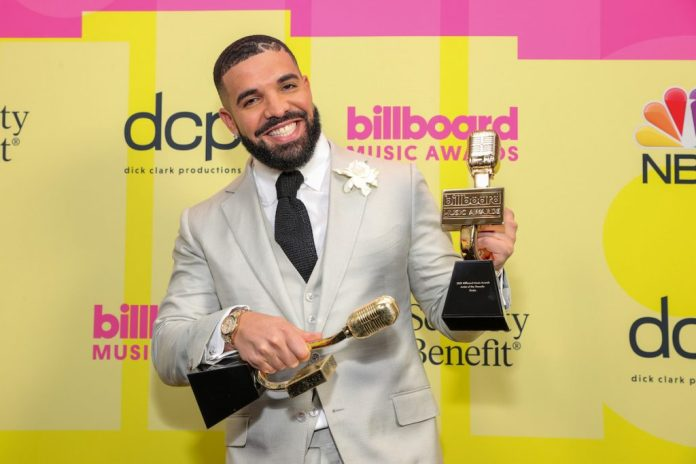 Smiling as the winner of the Artist of the Decade award poses with the awards in a Drake cream suit, poses backstage for the 2021 Billboard Music Awards, which airs May 23, 2021 at the Microsoft Theater in Los Angeles, California .
