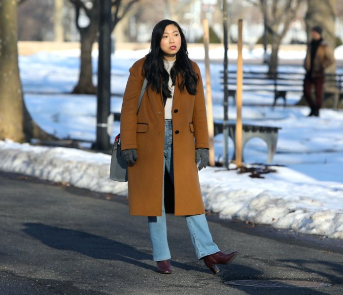 Awkwafina wears a brown coat and jeans during the shooting of a scene in 'Awkwafina Is Nora From Queens' in 2021.