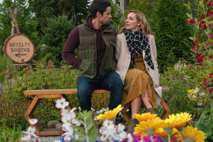 Ben Hollingsworth as Dan Brady and Zibby Allen as Brie Sheridan sitting on a park bench in 'Virgin River'