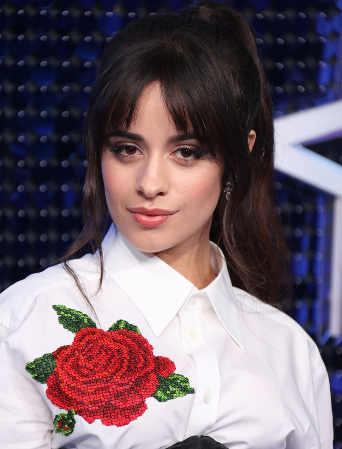 Camila Cabello wears a white top with a big red rose to an event.