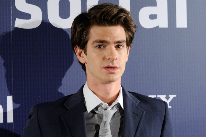 Andrew Garfield at a photocall for 'The Social Network' in 2010.  He wears a dark blue suit, gray vest and light gray tie as he stands in front of a uniform dark blue background with 'Social' and 'Sony' written in white.  Letter.  Garfield's