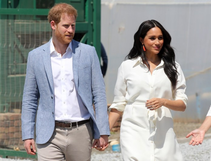 Prince Harry and Meghan Markle hold hands during a tour in Johannesburg, South Africa