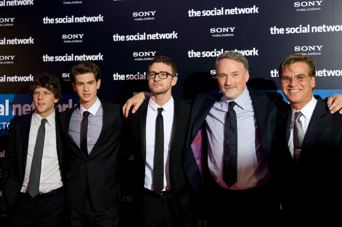 Jesse Eisenberg, Andrew Garfield, Justin Timberlake, David Fincher and Aaron Sorkin attend the premiere of 'The Social Network' in Paris.  The men stand side by side in black suits and with their arms tied around each other.  They stand in front of a background with 'The Social Network' and 'Sony' written in white letters.  Fincher directed three actors in the Oscar-winning film.  And Fincher is known to have actors perform multiple takes, which Garfield found tedious, but gratifying.
