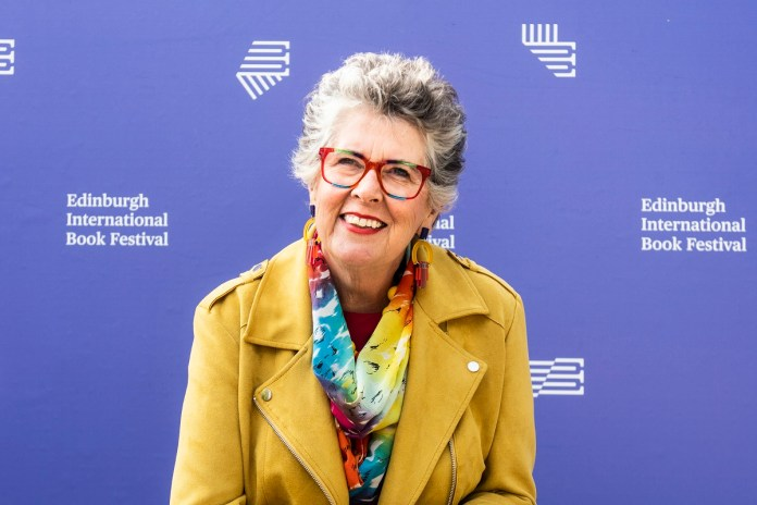 Prue Leith's Return to The Great British Baking Show Season 9 - Prue is wearing a yellow jacket and an iridescent scarf and glasses frame.