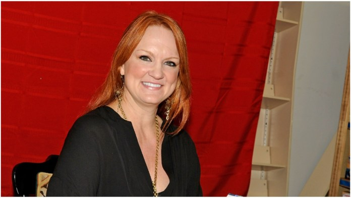Ree Drummond smiles in a black shirt against a red background