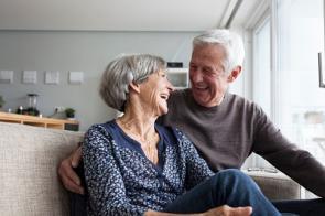 Älteres Paar sitzt im Wohnzimmer auf der Couch.