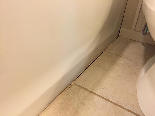 installing caulk strip over cracked grout