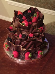 Multi-level, tiered cake filled with fluffy chocolate buttercream covered in ganache and enrobed in chocolate ruffles.