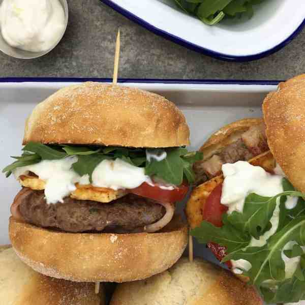 Lamb burgers with bacon & yoghurt dressing - lightly spiced lamb patties wrapped in bacon & dripping in a zingy yoghurt sauce