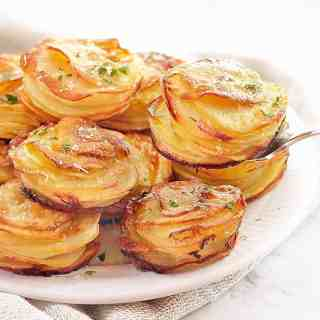 stacks of sliced cooked potato on a white plate