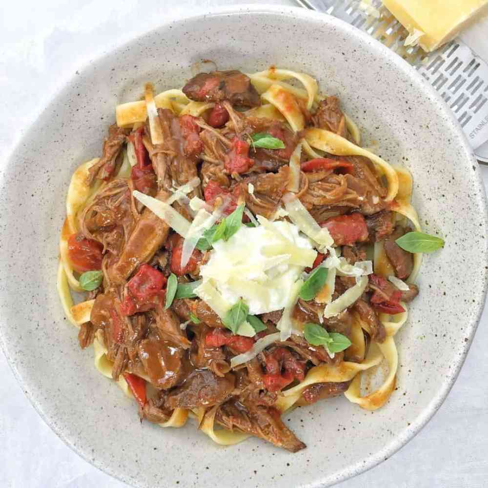 lamb with sauce on pasta in a white bowl